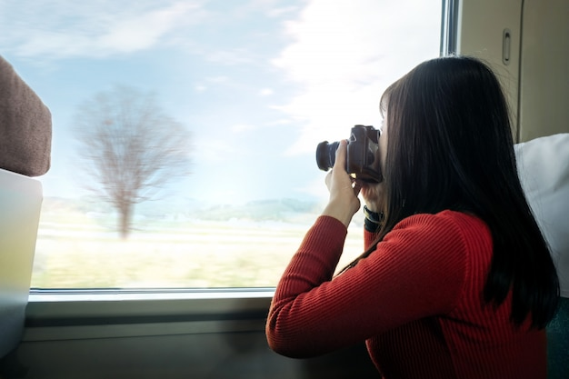 Travel concept. young traveling woman with camera taking photo while sitting in train