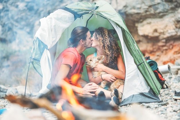 Travel couple kissing while sitting in the tent with their pet