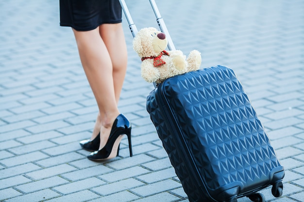 Travel, cropped young casual female goes at airport at window with suitcase waiting for plane