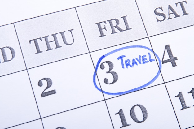 青いフェルトペンでカレンダーにマークされた旅行日金曜日を思い出させるためにカレンダーで丸で囲んだ...