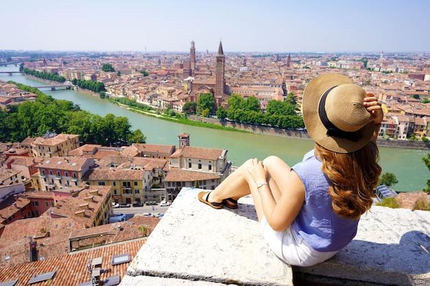 旅行先イタリア。イタリア、ヴェローナの素晴らしい景色を楽しみながら壁に座っている若い女性のベルヴェデーレから広角。