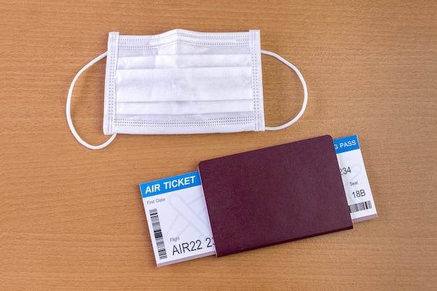 Covid-19パンデミックの間に旅行します。フェイスマスク、航空券、パスポート付きの飛行機モデル。休日の準備ができました。