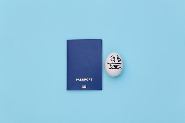 Covid-19 기간 동안 여행하십시오. 파란색 배경에 의료 마스크에 여권과 달걀 얼굴.