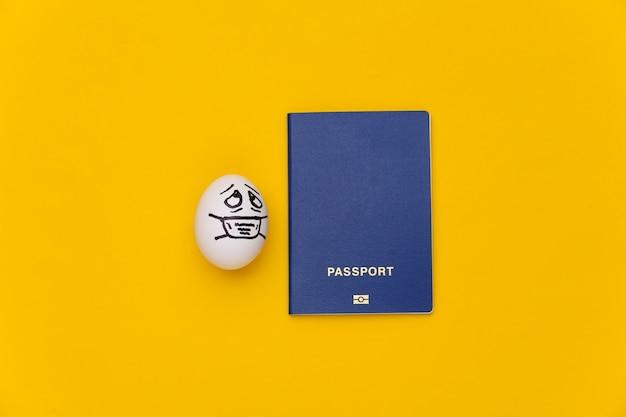 Covid-19 기간 동안 여행하십시오. 노란색 배경에 의료 마스크에 여권과 달걀 얼굴.