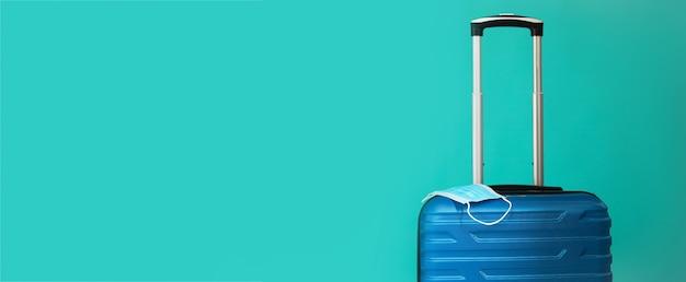 Covid-19の期間中に旅行します。青い背景に医療マスクと青いスーツケース。テキストコピースペース用の空きスペース。休暇、コロナ時代の休日。