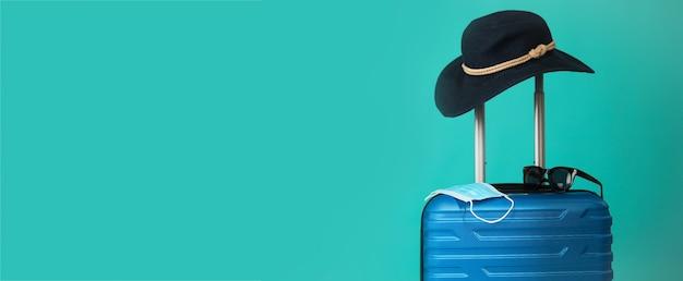Covid-19の期間中に旅行します。青い背景に医療マスク、サングラス、帽子と青いスーツケース。テキストコピースペース用の空きスペース。休暇、コロナ時代の休日。