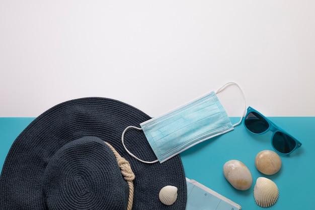 Covid-19 기간 동안 여행하십시오. 파란색과 흰색 배경에 의료 마스크, 선글라스, 모자, 조개. 텍스트를 위한 여유 공간입니다. 휴가, 코로나 시대의 휴일. 화려한 디자인.
