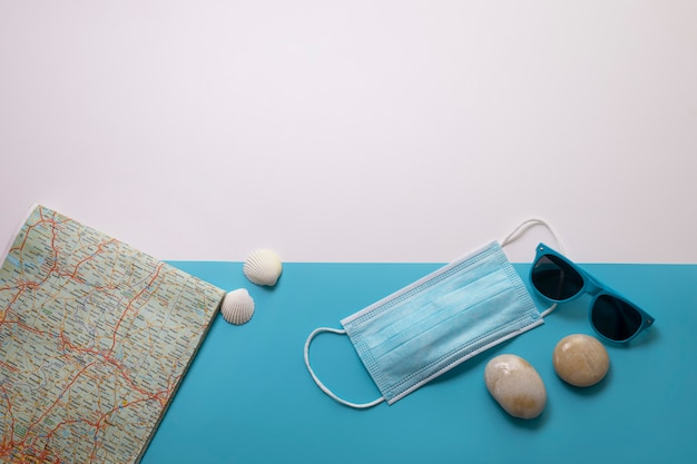 Covid-19 기간 동안 여행하십시오. 파란색과 흰색 배경에 의료 마스크, 선글라스, 지도, 조개. 텍스트를 위한 여유 공간입니다. 휴가, 코로나 시대의 휴일. 화려한 디자인.