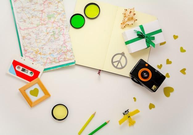写真カメラ、飛行機のおもちゃ、地図、ノートブック、平和のシンボルおよびその他の要素と旅行要素の構成