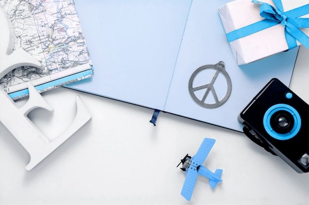 Travel elements composition with photo camera, airplane toy, map, photo album, peace symbol