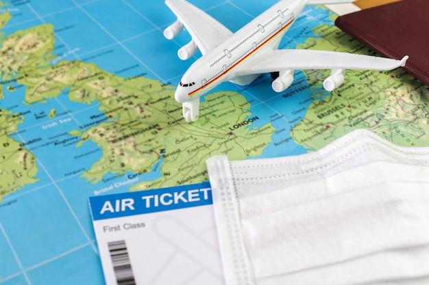 Covid-19パンデミックの間にイギリスを旅行します。フェイスマスク、航空券、パスポート付きの飛行機モデルの地図上のロンドン。休日の準備ができました。旅行のコンセプト