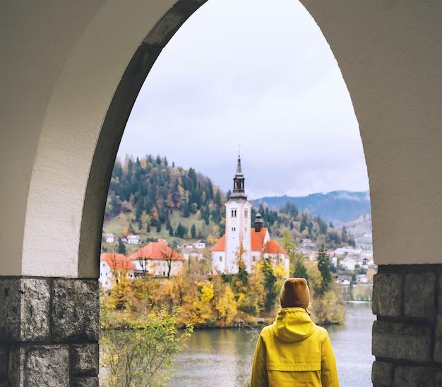Путешествие по европе турист в желтом плаще смотрит на остров с церковью на озере блед в словении