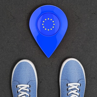 Travel to european union concept. blue denim sneakers on the asphalt road with map pointer and eu flag top view extreme closeup. 3d rendering
