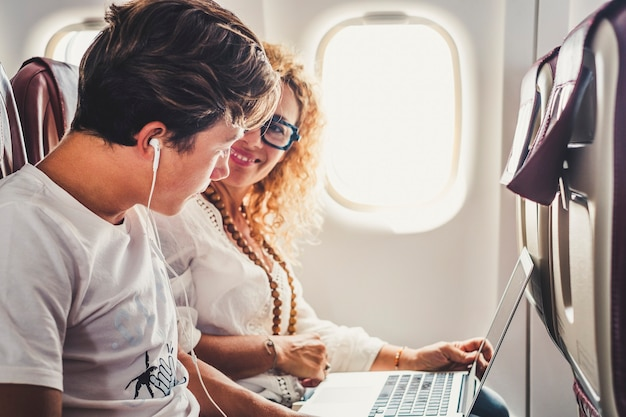 여행 가족 부부 성인 어머니와 십 대 아들이 기내에서 인터넷에 연결된 컴퓨터 노트북과 함께 비행을 즐기는 비행기에 함께 여행