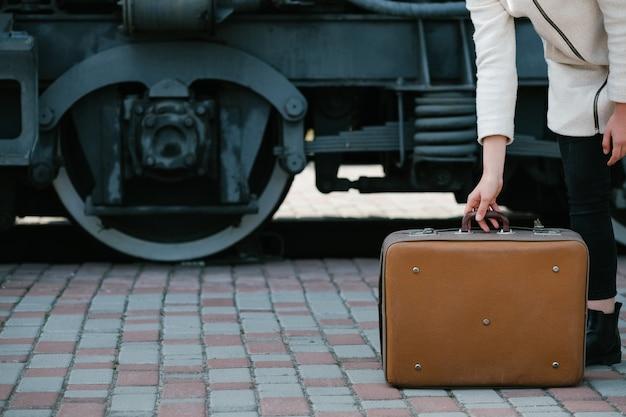 旅行ファッションアクセサリー。流行に敏感なヴィンテージレトロスーツケーススタイル。輸送の旅の目的地。駅の女性。自由空間の概念