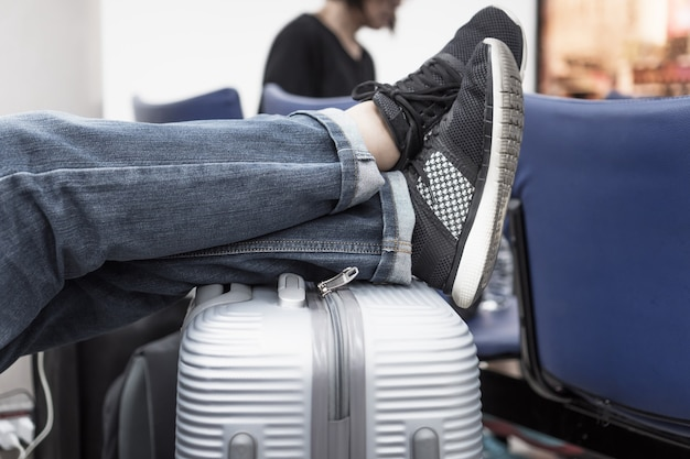 Travel feet on suitcase luggage at international airport when delayed or canceled flight. trip vacation or holiday tourism concept