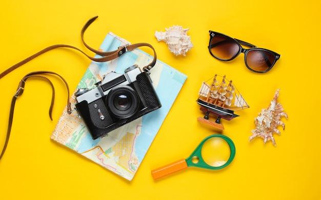 旅行フラット横たわっていたアクセサリーと黄色のレトロなカメラ