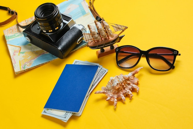 Travel flat lay accessories and retro camera on yellow