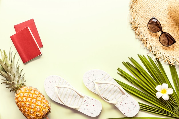 Travel flat lay items: fresh pineapple, two passports, big straw hat, sunglasses, tropical flower plumeria and palm leaf.