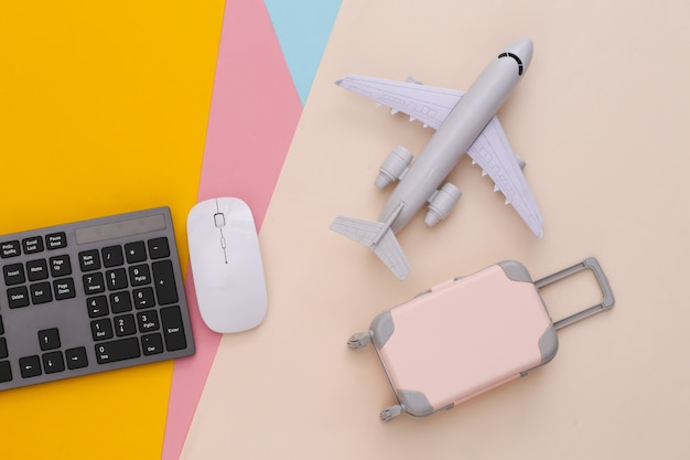 Travel flat lay. pc keyboard and mini travel luggage, air plane on colored table