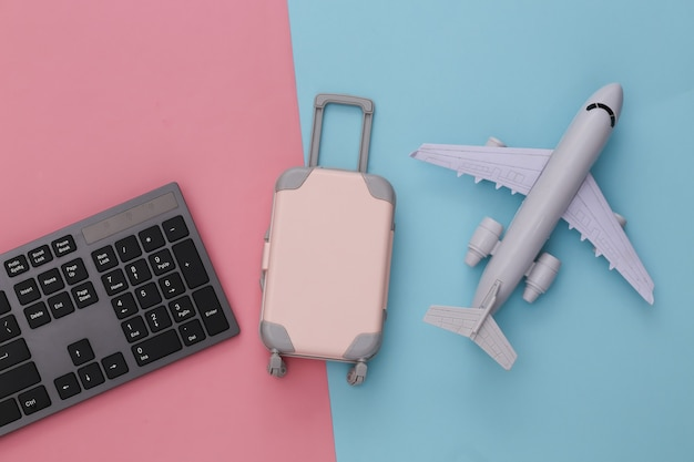 Travel flat lay. pc keyboard and mini travel luggage, air plane on pink blue