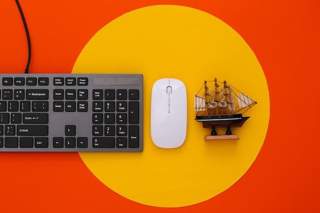 Travel flat lay pc keyboard and ship on orange with yellow circle