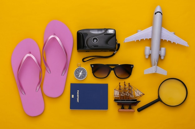 여행 평면 누워. 노란색 배경에 여행 액세서리입니다. 최소한의 스타일. 평면도