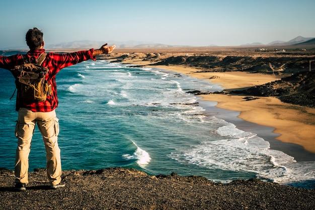 代替の人々のための旅行休日夏休みの目的地彼の前の自然の素晴らしいビーチで成功と喜びのために腕を操作するバックパックを背負って後ろから男と