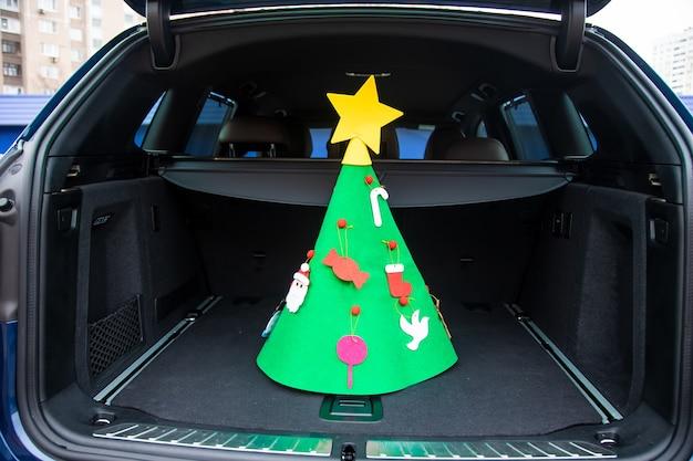 새해 휴가 여행. 장난감과 별이 장식된 펠트 크리스마스 트리가 현대식 크로스오버의 빈 트렁크 중앙에 서 있습니다. 클로즈업, 소프트 포커스