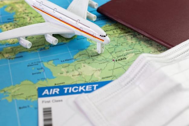 Covid-19パンデミックの間にフランスを旅行します。フェイスマスク、航空券、パスポート付きの飛行機モデルの地図上のパリ。休日の準備ができました。旅行のコンセプト