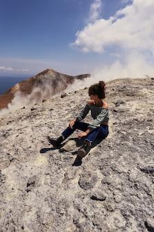 여행 소녀 젊은 여성 블로거는 산 꼭대기에 앉아서 앞을 바라보고 있습니다.