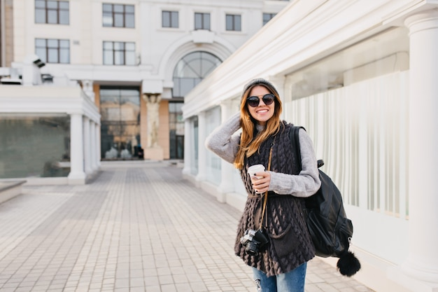 Travel happy time in modern city centre of yoyful pretty young woman in sunglasses, warm winter woollen sweater, knitted hat. travelling with backpack, coffee to go, camera. place for text.