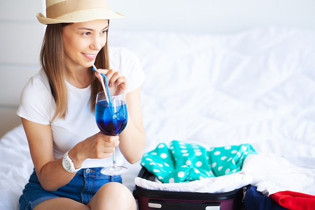 Travel, happy woman is packing suitcase at home