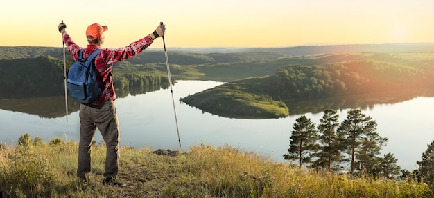 Travel hiking man looking at nature landscape sunset panoramic banner background. traveling lifestyle adventure concept.