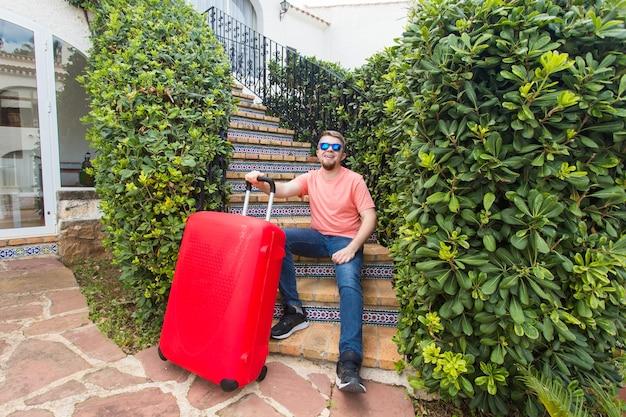 여행, 휴가 및 사람들 개념-행복 잘 생긴 남자 관광 가방 계단에 앉아 웃 고.
