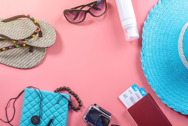 Travel holiday supplies: hat, sunglasses, camera passport and airline tickets on pink background