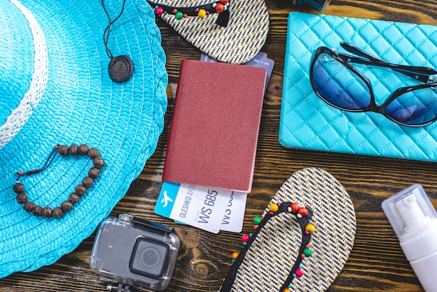 Travel holiday supplies: hat, sunglasses, flip flops, camera passport and airline tickets on old wooden background.