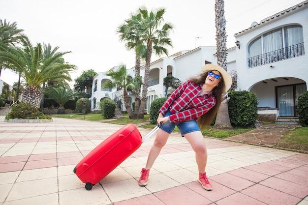 旅行、休日、人々のコンセプト。彼女の重いスーツケースを引っ張って笑っている面白い女性。
