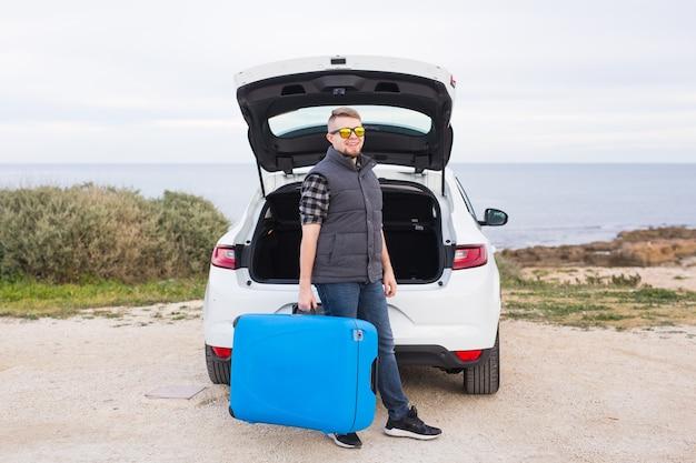 Концепция путешествий, праздников и отпуска. мужчина возле машины с синим чемоданом.