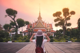Travel in Bangkok concept. Woman in hat at Wat arun temple