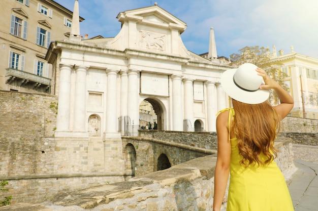 Путешествие по италии. вид сзади красивой девушки, посещающей ворота порта сан джакомо в городе бергамо в солнечный день. летний отдых в италии.