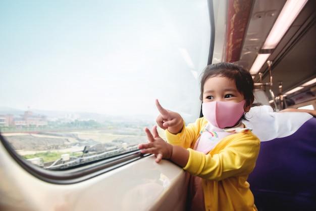 新しい通常のライフスタイルコンセプトで旅行します。彼女の親と一緒に旅行中に電車の中で外科用保護マスクを着て幸せな子供たち。ワイドガラスの窓際に座って眺めを楽しむ