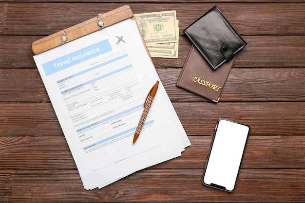 Travel insurance form with money, passport and mobile phone on table
