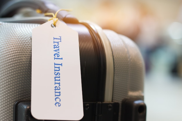 Travel insurance tag on suitcase holder with tag tied letters enjoyable your trip on bag