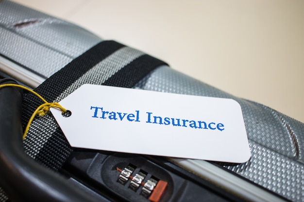 Travel insurance tag on suitcase near numeric combination lock with tag tied letters enjoyable trip