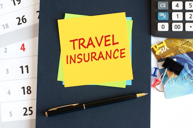 Travel insurance, text on yellow paper square shape. notepad, calculator, credit cards, pen, stationery on the desktop. business, financial and education concept. selective focus.