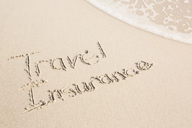 Travel insurance written on sand Free Photo