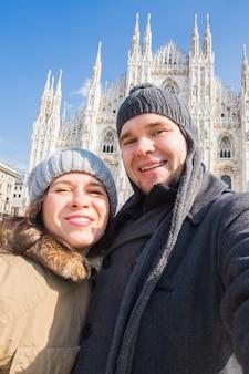 旅行、イタリア、面白いカップルのコンセプト-ミラノのドゥオーモ大聖堂の前で鳩と自画像を撮る幸せな観光客