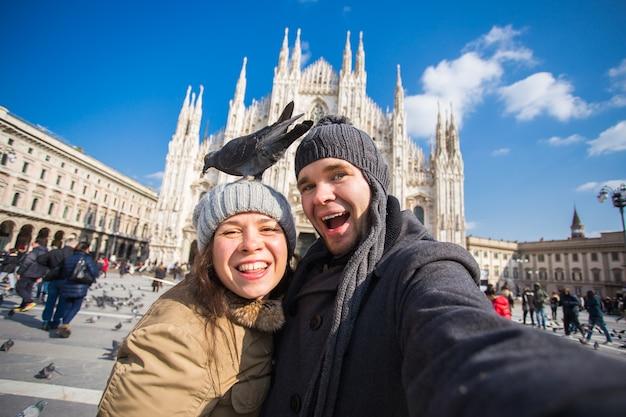 Путешествие, италия и концепция смешной пары - счастливые туристы, делающие автопортрет с голубями