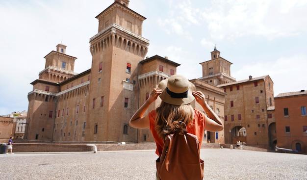 Travel in italy. back view of beautiful tourist girl enjoying view of este castle (castello estense) of ferrara, italy.